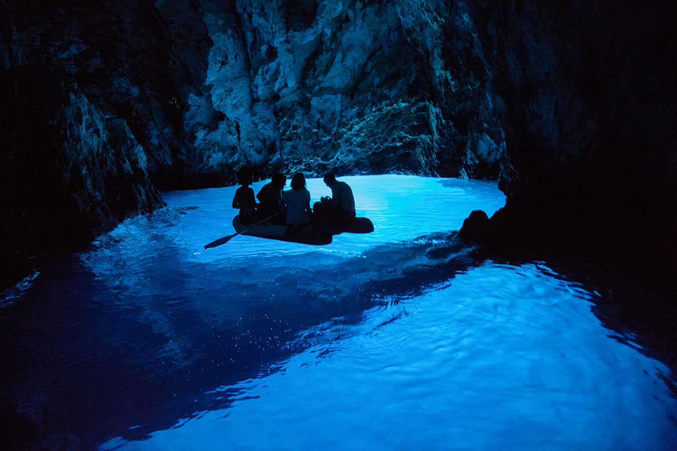 Blue cave with water illuminated from the bottom.