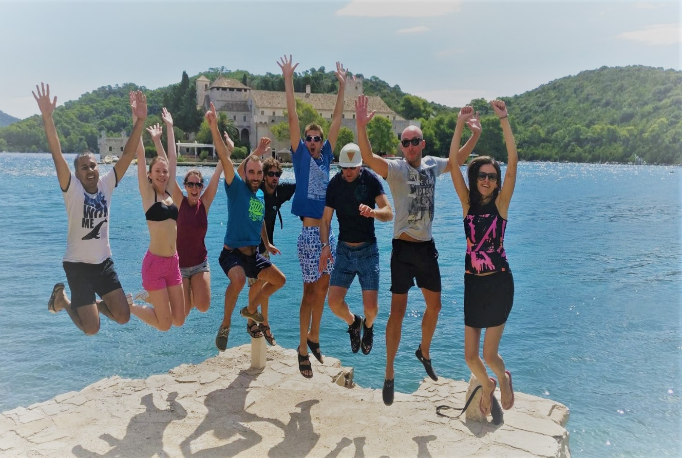 A group of people jumping together on a rock. Croatian blue water in the background.